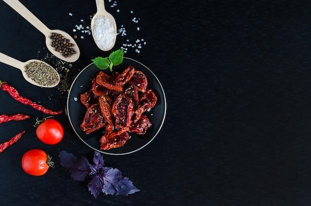 Домашние вяленые помидоры с оливковым маслом, морской солью, базиликом, орегано специями на темном фоне. процесс приготовления традиционной итальянской средиземноморской кухни. вид сверху, плоская планировка, копирование пространства, текст