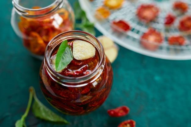 自家製サンドライトマトハーブ、濃い緑色の背景にガラスの瓶にオリーブオイルでニンニク。上面図。キッチン用プリント
