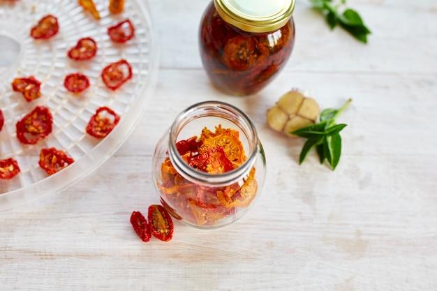 自家製サンドライトマトとハーブ、白い木製の背景にガラスの瓶にオリーブオイルでニンニク。上面図。キッチン用プリント