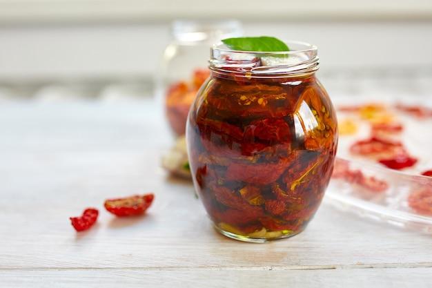 ハーブと自家製サンドライトマト、ガラスの瓶にオリーブオイルでニンニク