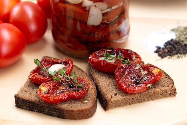 ガラスの瓶にオリーブオイルを入れた自家製サンドライトマト。黒パンとサンドライトマトのサンドイッチ。