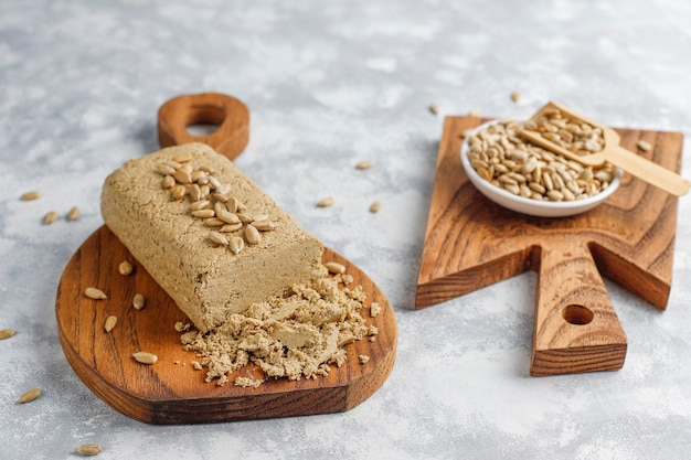 Homemade sunflower halva on cutting board with sunflower seeds