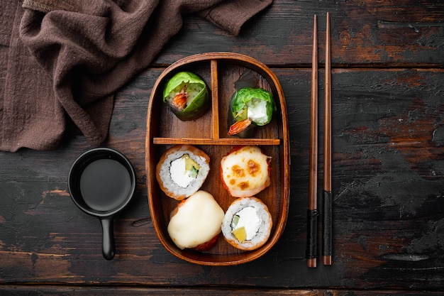 Самодельная коробка для суши-бенто с набором суши-роллов на старом темном деревянном столе