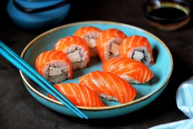 Домашние суши-роллы филадельфия и нигири в синей тарелке на черной поверхности.