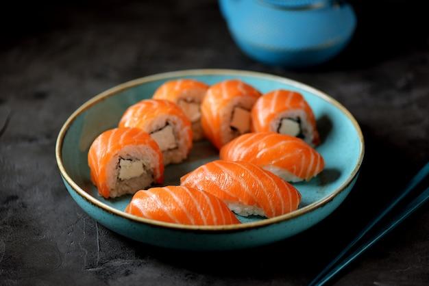 自家製寿司はフィラデルフィアとにぎりを黒い表面の青い皿に巻きます。
