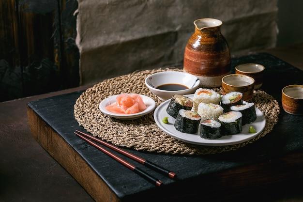 연어, 일본 오믈렛, 아바 카도, 생강, 간장으로 만든 수제 스시 롤과 밀짚 냅킨에 젓가락을 얹습니다. balck 나무 테이블. 도자기 술 세트. 일본식 저녁