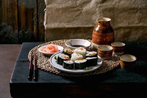 수제 스시 롤은 연어, 일본 오믈렛, avacado, 생강 및 검은 나무 테이블 위에 밀짚 냅킨에 젓가락으로 간장으로 설정합니다. 도자기 술 세트. 일본식 저녁