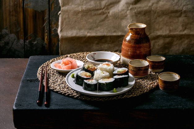 Homemade sushi rolls set with salmon, japanese omelette, avacado, ginger and soy sauce with chopsticks on straw napkin over black wooden table. ceramic sake set. japanese style dinner