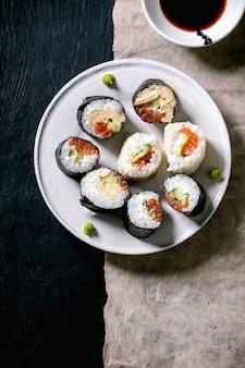 Самодельные роллы суши с лососем, японским омлетом, авакадо, васаби и соевым соусом на серой бумаге на черном деревянном фоне, вид сверху, плоская планировка. ужин в японском стиле