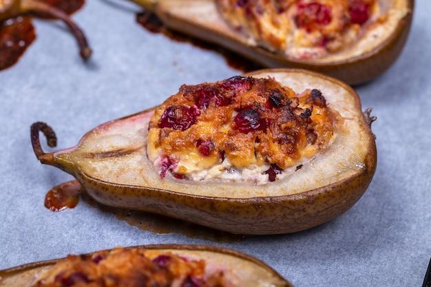 蜂蜜、クルミ、クランベリー、シナモンを添えた自家製の甘い焼き梨をクローズアップ。キャラメルとジャムで焼いた甘い公爵夫人梨のデザート