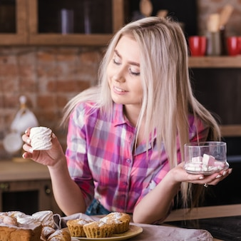 수제 달콤한 빵집. 머랭과 신선한 머핀 파이와 접시와 함께 포즈를 취하는 아름 다운 금발 여성. 프리미엄 사진