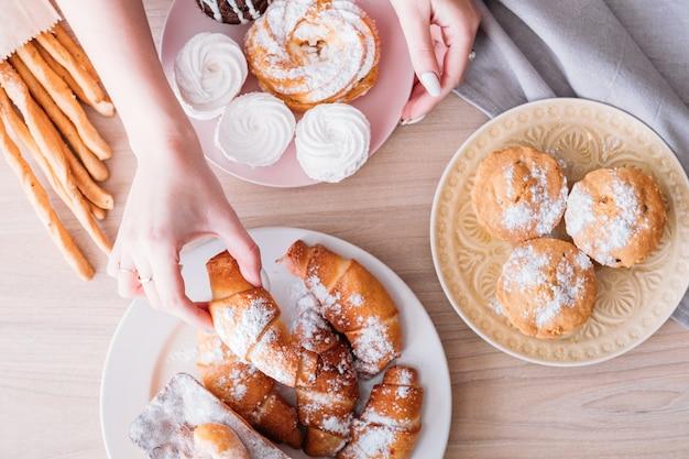 수제 달콤한 빵집. 테이블에 디저트 구색. 신선한 파이 접시에서 크루아상을 복용하는 여자.