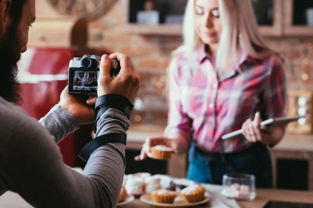수제 달콤한 빵집. 음식 사진. 신선한 케이크와 파이 금발 여자의 사진을 찍는 남자.