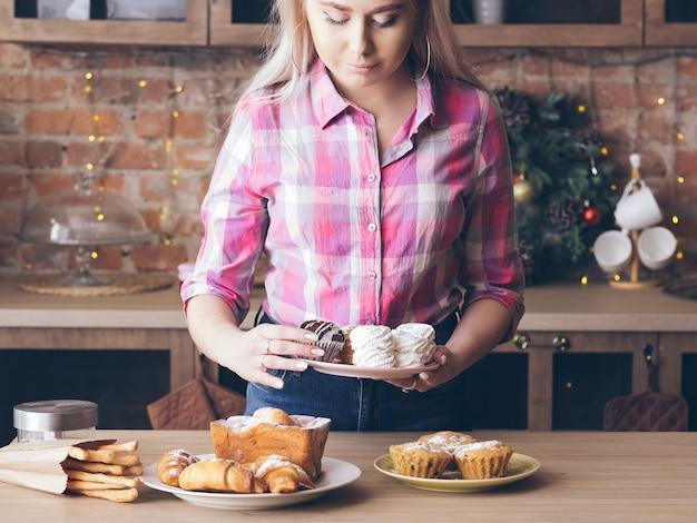 수제 달콤한 빵집. 푸드 스타일리스트. 신선한 파이와 접시를 정렬하는 여성. 머랭, 머핀 및 과일 케이크.