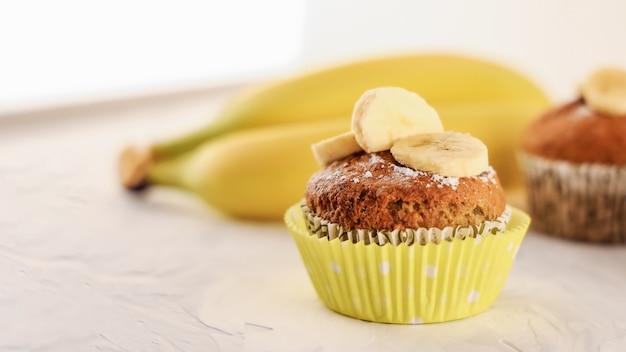 노란색 바나나 배경에 대리석 테이블에 만든 달콤한 바나나 머핀