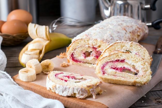 Домашний сладкий бисквитный рулет со сливками и фруктами на деревянном столе