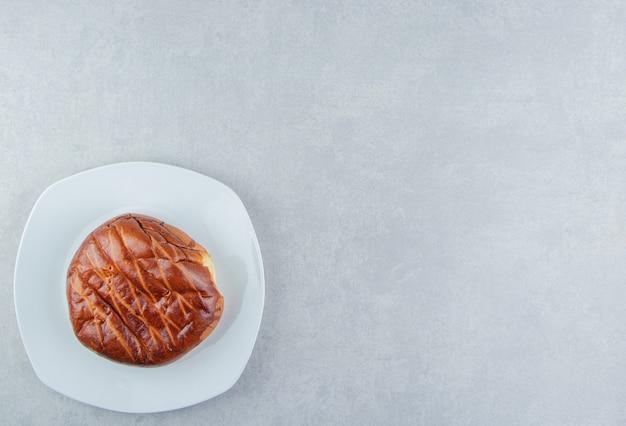 Домашняя сладкая булочка на белой тарелке.