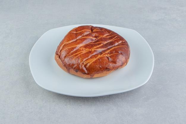 Homemade sweet bun on white plate.