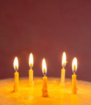 キャンドルで記念日のための自家製の甘いケーキ
