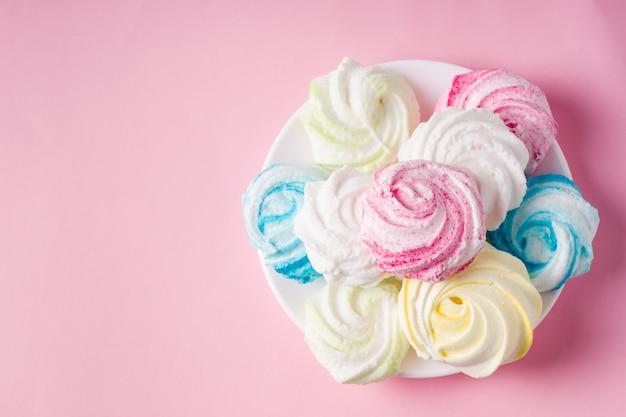 白い背景の上の自家製の甘い色のメレンゲ。デザート。