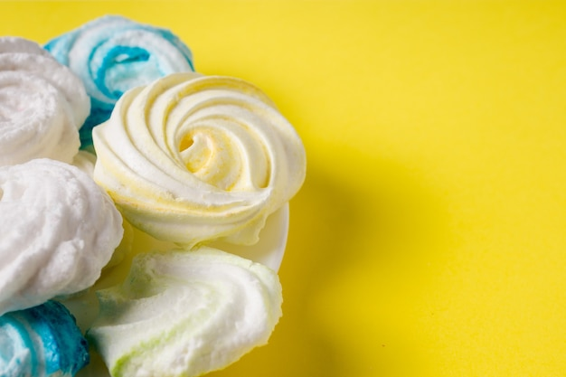 黄色の背景に自家製の甘い色のメレンゲ。デザート。