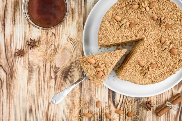 Домашний сладкий слоистый медовый торт с орехами на белой плите на деревянном столе с миской меда, корицы и бадиана.