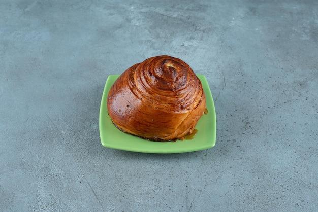 Домашнее сладкое тесто на зеленой тарелке.