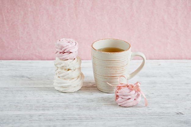 自家製の甘いピンクと白のマシュマロ-軽い木製のテーブルのゼファー。
