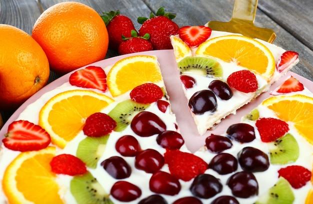 木製のテーブルにフルーツと自家製の甘いピザ、クローズアップ
