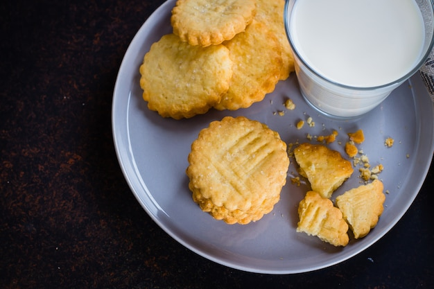 Homemade sweet sugar shortbread cookies with milk on dark stone concrete table background