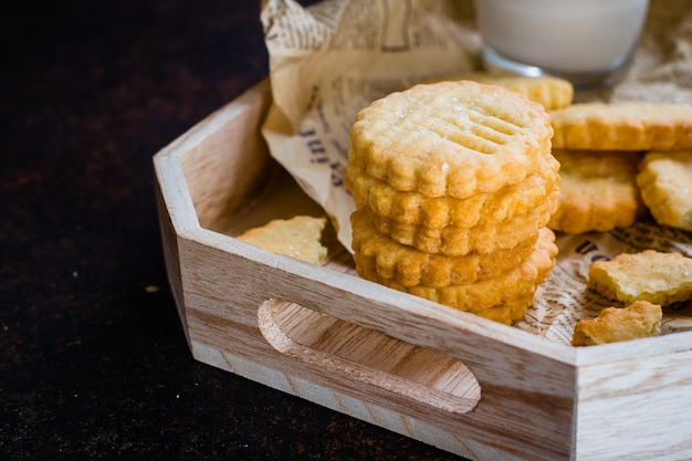 Homemade sweet sugar shortbread cookies with milk on dark stone concrete table