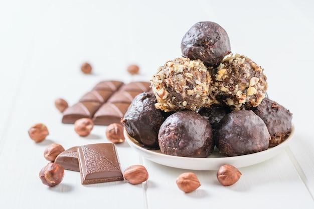 Домашние сладости из орехов, сухофруктов, шоколада и меда на тарелке на белом столе и шоколадной плитке.