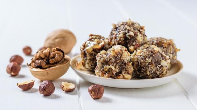 Домашние сладости из орехов, сухофруктов, шоколада и меда на тарелку на белом столе.