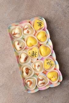 アーモンドとカボチャの種を含む、ウコン抽出物で着色されたホワイトチョコレートで作られた自家製のお菓子
