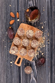 Homemade sweets on a wooden cutting board with ingredients, top view.