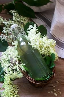 ガラスの瓶にニワトコの花と木製のテーブルの高齢者の枝の自家製シロップ素朴なスタイル。