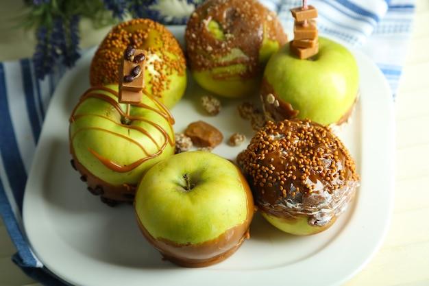 Домашние яблоки ириски, на салфетке, на деревянном фоне
