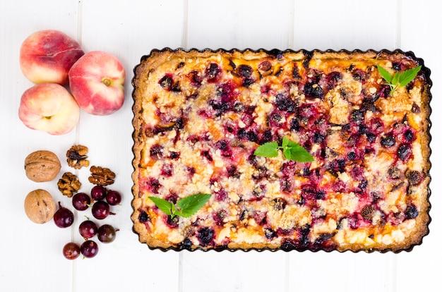 Домашний пирог с ягодами, фруктами и грецкими орехами в форме на светлом фоне.
