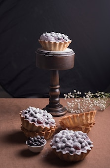 Homemade tart with berries and whipped cream on brown desk against black background