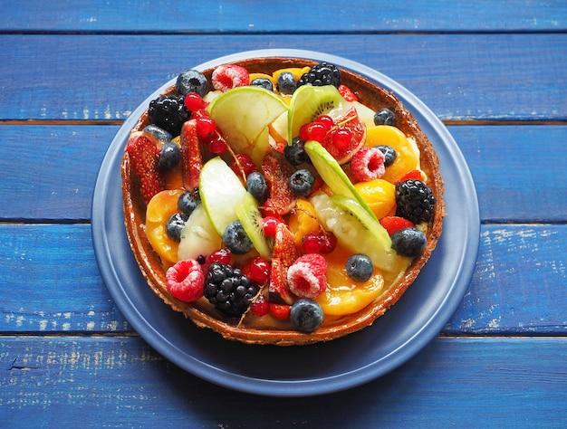 青い木製のテーブルにエキゾチックなフルーツとベリーの自家製タルト