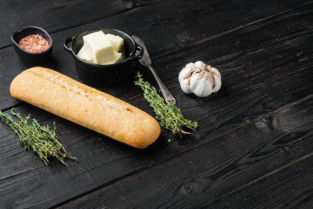 검은색 나무 테이블 배경에 마늘과 허브 재료를 넣은 홈메이드 맛있는 빵, 텍스트 복사 공간