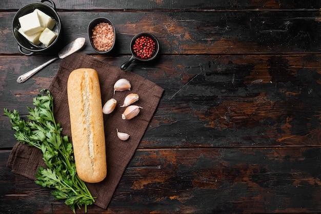 오래된 어두운 나무 테이블 배경에 마늘과 허브 재료를 넣은 홈메이드 맛있는 빵, 텍스트 복사 공간이 있는 평면도