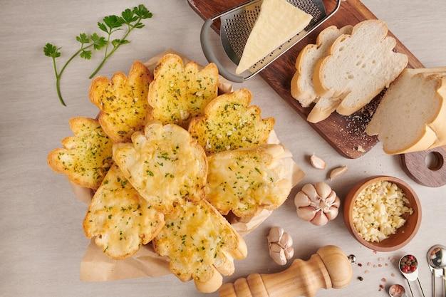 キッチンテーブルにニンニク、チーズ、ハーブを添えた自家製のおいしいパン。