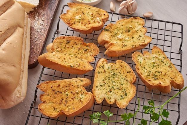 キッチンテーブルにニンニク、チーズ、ハーブを添えた自家製のおいしいパン。 無料写真
