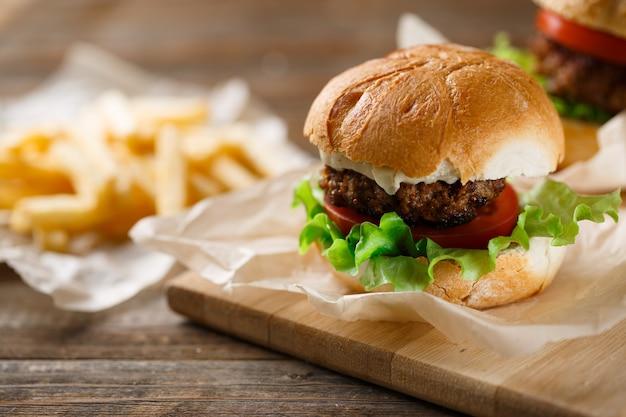 나무 테이블에 홈메이드 맛있는 버거와 감자튀김