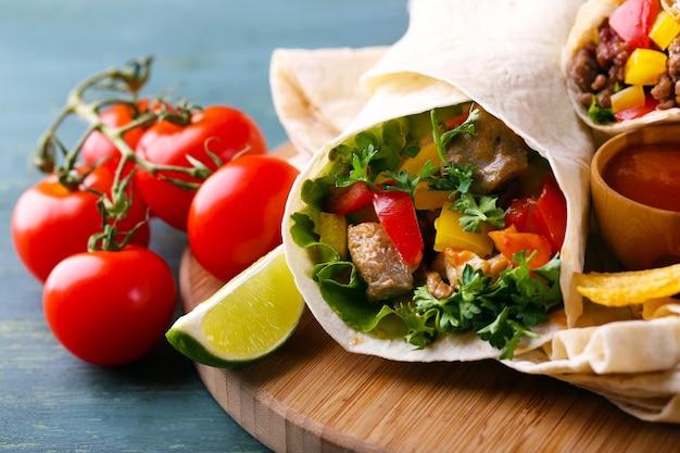 自家製のおいしいブリトーと野菜、まな板のポテトチップス、木製のテーブル