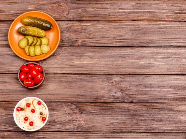 소금에 절인 양배추, 토마토, 피 클, 나무 테이블에 접시-복사 공간에 만든 맛있는 발효 우유 제품. 평평하다.