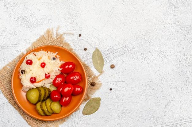 소금에 절인 양배추, 토마토, 피클, 후추, 베이 리프-접시에 직접 만든 맛있는 발효 제품