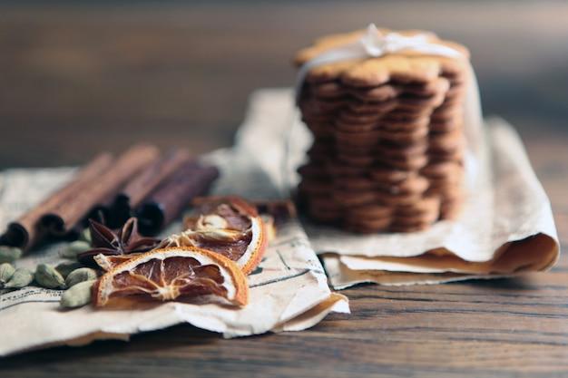 어두운 소박한 나무 테이블에 집에서 만든 맛있는 진저 쿠키는 공간을 복사합니다. 건강한 채식주의 유기농 영양 개념. 말린 오렌지, 계피, 오래된 종이, 향신료 및 허브를 곁들인 곡물 쿠키.