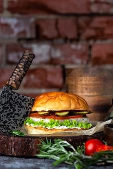木の板に新鮮な野菜を添えた自家製のおいしいハンバーガー